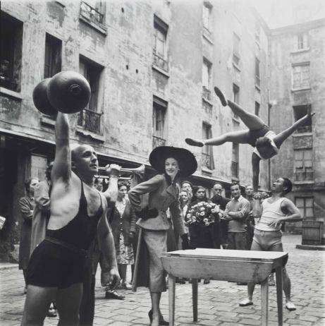 Elise Daniels com artistas de rua, traje por Balenciaga, Le Marais, Paris, 1948. Foto de Richard Avedon.